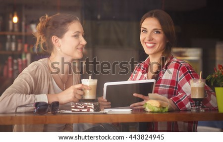 Toned image of best friends communicating or talking while sitting in restaurant or cafe. Ladies looking at tablet PC.