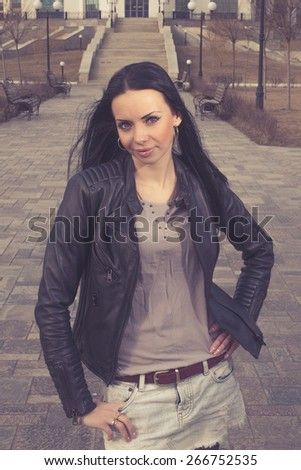 Toned image of brunette women posing outdoors in city park front view shot. She is posing in city park with stairway on background with her hand on waist.