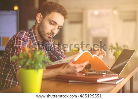 Toned image of handsome student man studying in front of laptop computer reading book or magazine in restaurant or cafe.