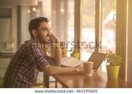 Toned image of happy handsome man speaking over phone while working in restaurant or cafe on his laptop computer. Business or freelance concept.