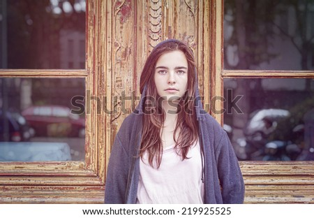 toned image, portrait of a teenager girl in front of a old wooden door with windows. - stock photo