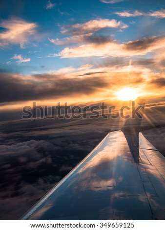 Toned image view from the window of an airplane to the Chinese mountains in winter on a background of sunset with clouds - stock photo