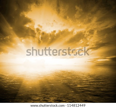toned orange landscape with sun, dramatic cloudy sky and sea with waves at sunset (sunrise) - stock photo