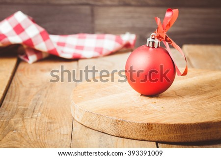 Toned photo. Color tone tuned. Red christmas ball on wooden background - stock photo