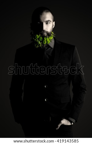 Toned photo of a handsome man with a beard of green flowers. Men's beauty. Barbershop. - stock photo