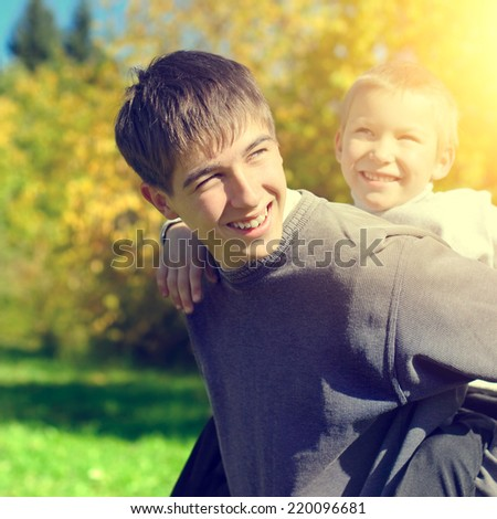 Toned photo of Cheerful Teenager and Kid at the Autumn Park - stock photo