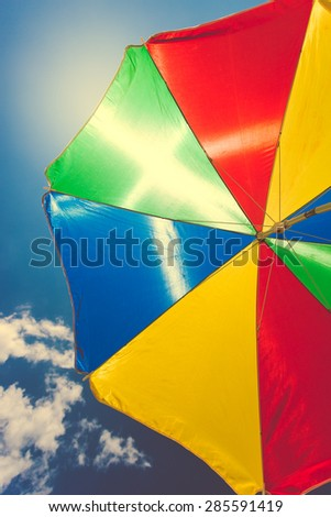 Toned photo of colorful umbrella against blue sky