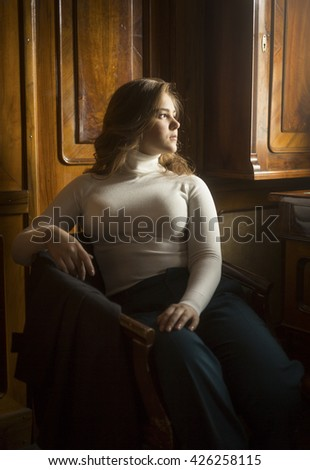 Toned photo of elegant young woman posing at wooden armchair and looking out of window - stock photo
