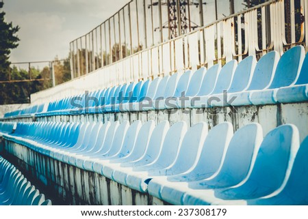 Toned photo of empty rows of seats on old stadium - stock photo