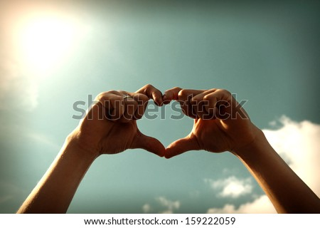 Toned Photo of Hands in Heart Shape on Sky Background - stock photo