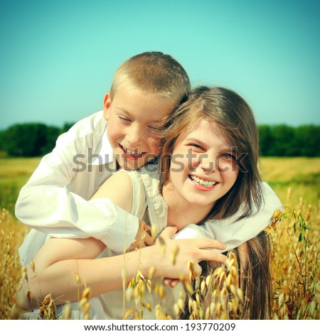 Toned photo of Happy Brother and Sister in the Wheat Field