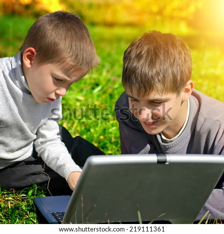 Toned photo of Happy Brothers with Laptop outdoor - stock photo