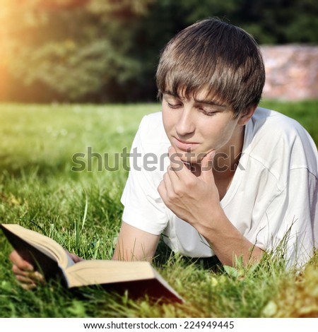 Toned Photo of Happy Teenager reads the Book on the Meadow - stock photo