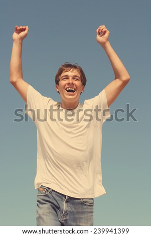 Toned Photo of happy teenager running on blue sky background - stock photo