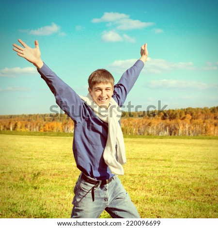 Toned photo of Happy Teenager with Hands Up running at the Autumn Field