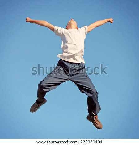 Toned photo of Happy Tennager jumping on the Sky Background - stock photo