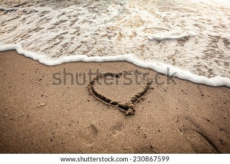 Toned photo of heart drawn on sand being washed by sea wave - stock photo