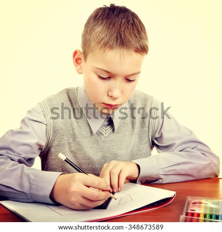 Toned Photo of Kid Drawing at the School Desk - stock photo