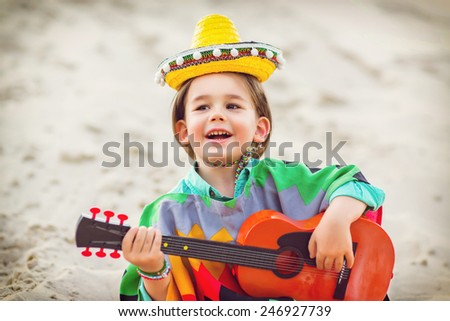 Toned photo of Little happy smiling boy plays his guitar or ukulele - stock photo