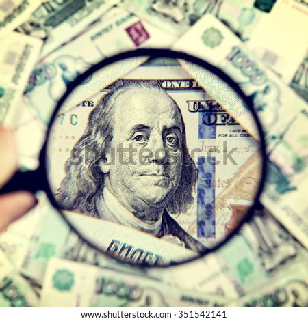 Toned Photo of Magnifying Glass on the American Dollars Background - stock photo