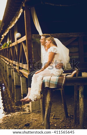 Toned photo of newly married bride and groom sitting on old pier and looking at sunset - stock photo
