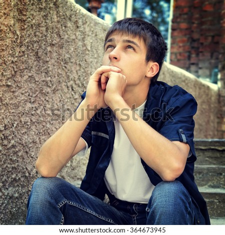 Toned Photo of Pensive Teenager sit on the Street - stock photo