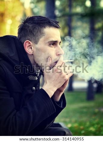 Toned Photo of Sad Man smoking Cigarette in the Autumn Park - stock photo