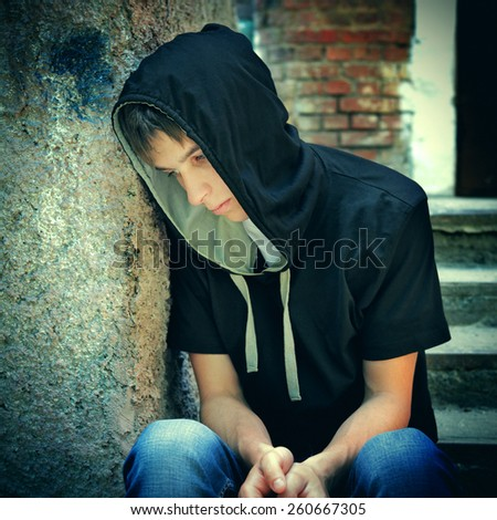 Toned Photo of Sad Teenager on the landing steps of the Old House - stock photo