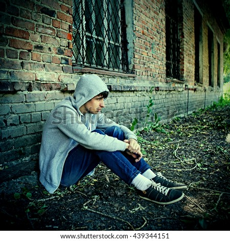 Toned Photo of Sad Teenager sit near the Brick Wall of the Old House - stock photo