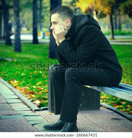 Toned Photo of Sad Young Man on the Bench in the Park - stock photo