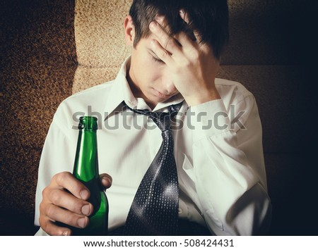 Toned Photo of Sad Young Man with Bottle of the Beer on the Sofa