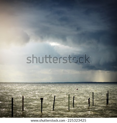 Toned Photo of Seaside Landscape with Thunderstorm Clouds - stock photo