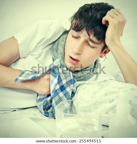 Toned Photo of Sick Young Man is Sneezing on the Bed with Handkerchief - stock photo