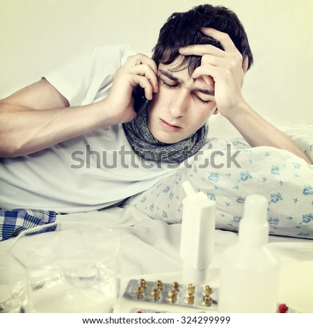 Toned Photo of Sick Young Man talk on Cellphone in the Bed - stock photo