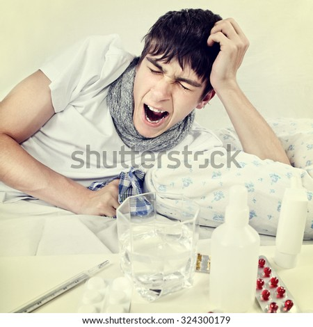 Toned Photo of Sick Young Man Yawn on the Bed - stock photo