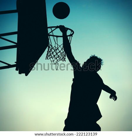 Toned Photo of Silhouette a Basketball Player on the Sky Background - stock photo