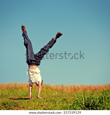 Toned photo of Somersault on the Grass of Teenager - stock photo