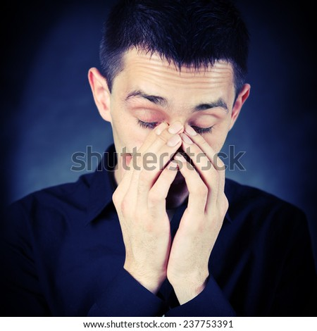 Toned Photo of Sorrowful Young Man on The Dark Background - stock photo
