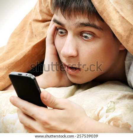 Toned Photo of Surprised Teenager with Cellphone under Blanket on the Bed - stock photo