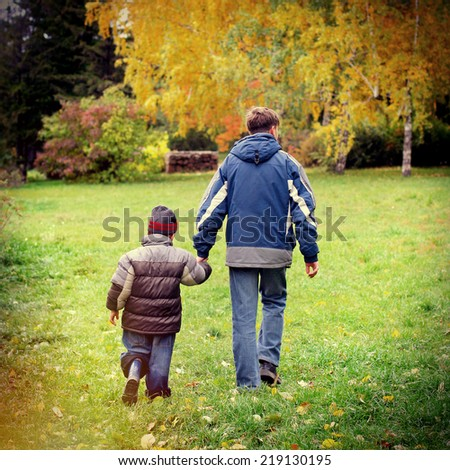 Toned photo of Teenager and Kid walking in the Autumn Park - stock photo