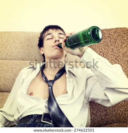 Toned Photo of Teenager drink a Beer on the Sofa at the Home - stock photo