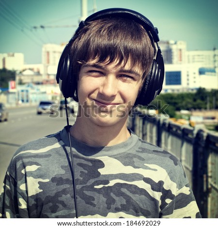 Toned photo of Teenager in Earphones on the Street - stock photo