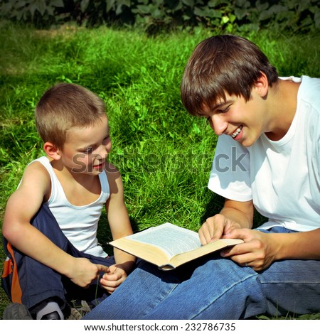 Toned photo of Teenager reads the Book to the Child - stock photo