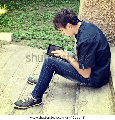 Toned Photo of Teenager with Tablet Computer on the landing steps - stock photo
