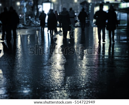 Toned Photo of the Defocused People on the Night Street
