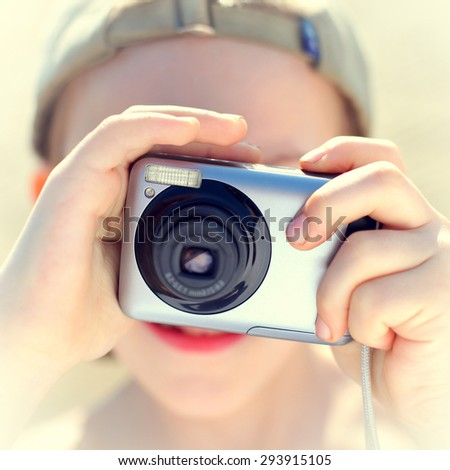 Toned photo of the Kid with Photo camera outdoor - stock photo
