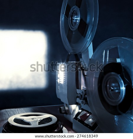 Toned Photo of the Old Film Projector in the Dark Room - stock photo