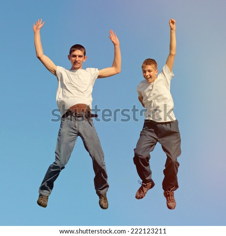 Toned photo of Two Happy Tennage Boys jumping - stock photo