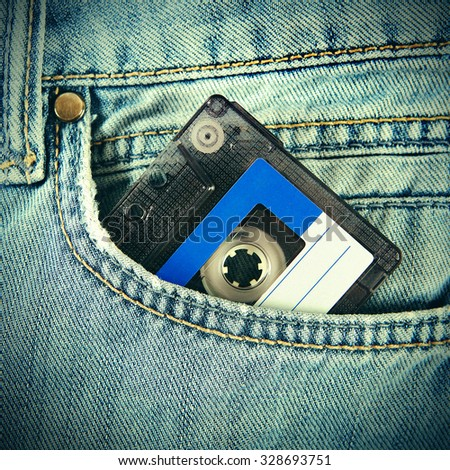 Toned Photo of Vintage Audio Tape Cassette in the Jeans Pocket closeup - stock photo