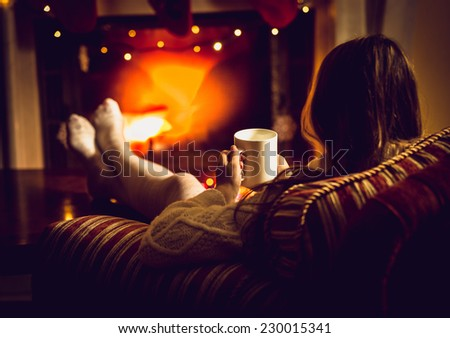 Toned photo of woman warming up with hot tea at fireplace at winter - stock photo